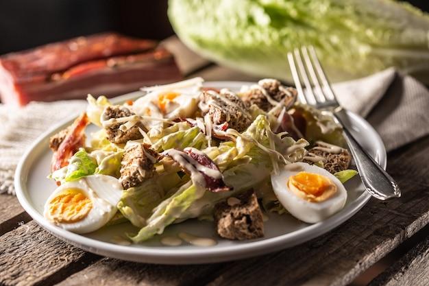 Caesar-salat mit gekochten eiern, speck und croutons auf einem teller serviert.