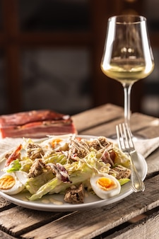 Caesar-salat mit gekochten eiern, speck und croutons, serviert auf einem teller neben einem glas weißwein.