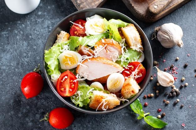 Caesar-salat mit geräuchertem huhn und parmesan auf einem teller auf dunklem hintergrund. ansicht von oben