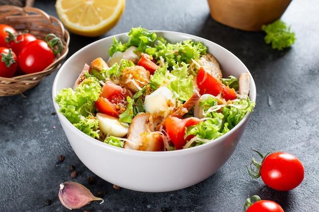 Caesar-salat mit geräuchertem huhn und parmesan auf einem teller auf dunklem hintergrund. platz kopieren.