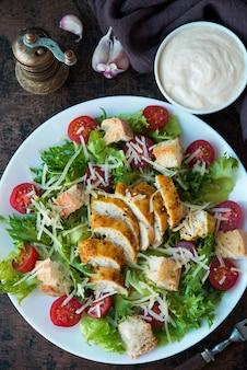 Caesar-salat mit hähnchenbrust, croutons und parmesansoße auf einem holztisch, ansicht von oben