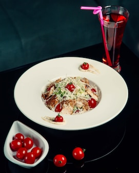 Caesar salat mit hühnchen, geriebenem käse und tomaten