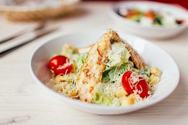 Caesar-salat mit huhn auf weißem holztisch mit gabel und messer.