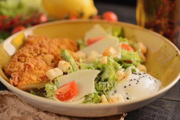 Caesar salat mit huhn, ei, parmesan und gemüse. in einer gelben platte auf einem holztisch