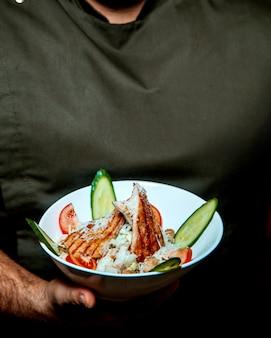 Caesar-salat mit huhn in den mannhänden