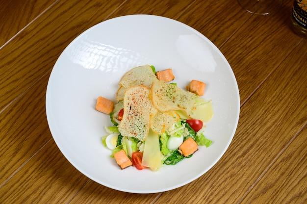 Caesar salat mit lachs auf weißem teller auf hölzernem hintergrund. caesar salat mit lachs, draufsicht