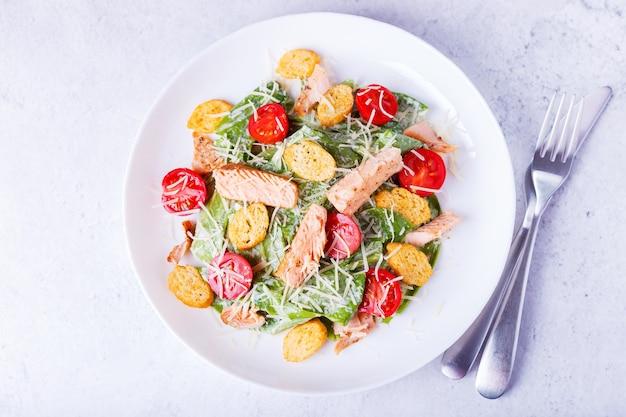 Caesar-salat mit rotem fisch (lachs, forelle), kirschtomaten, croutons, parmesan und römersalat. traditionelles amerikanisches gericht. nahaufnahme, selektiver fokus, ansicht von oben.