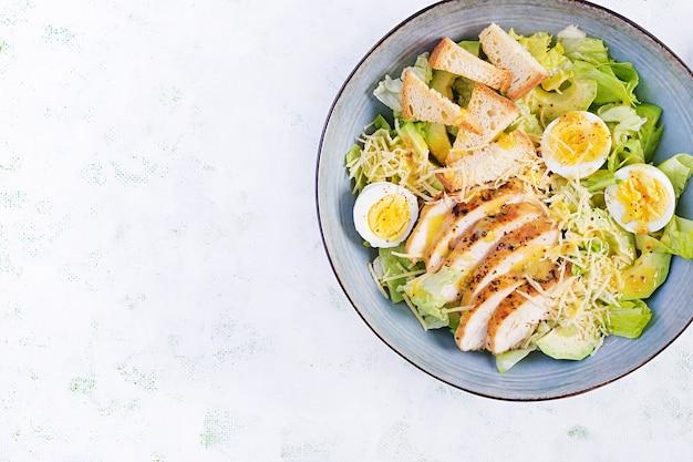 Caesar-salat mit salat, hühnchen, avocado und croutons auf leuchttisch