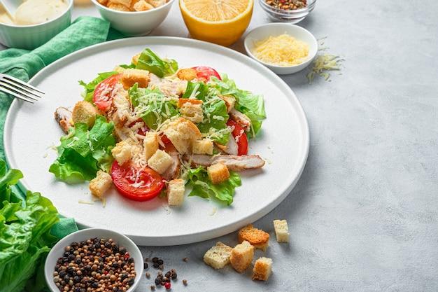 Caesar salat nahaufnahme auf einem weißen teller umgeben von zutaten auf einem grauen hintergrund. das konzept der gesunden ernährung.