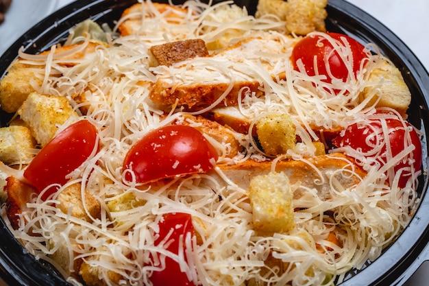 Caesar-salat von der seite mit gegrillten hähnchenbrot-zwieback-kirschtomaten und parmesankäse an der spitze