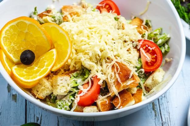 Caesar-salat von der seite mit tomatensalat-sauce brot zwieback gegrillter hühnerkäse schwarze olive und orange auf teller