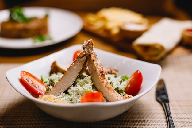 Caesar-salat von vorne mit hühnchen- und tomatenscheiben