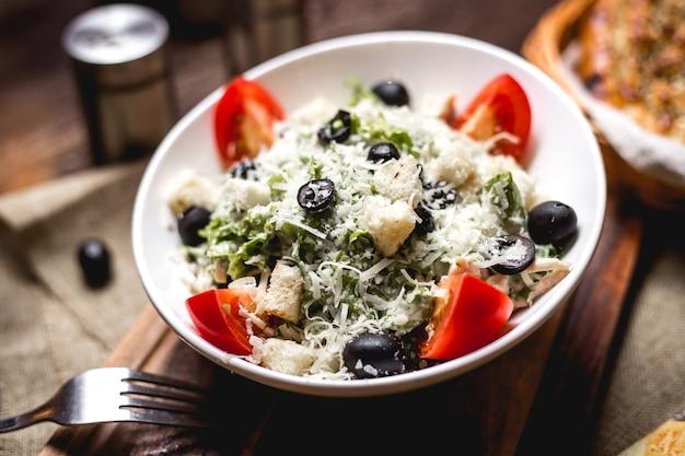 Caesar salatschüssel garniert mit geriebenem käse und oliven