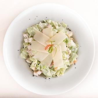 Caeser salad mit hühnerleiste, weiße platte, brauner hintergrund