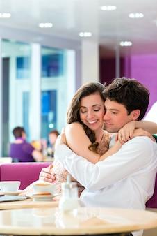 Café des jungen paares, das umarmt und küsst