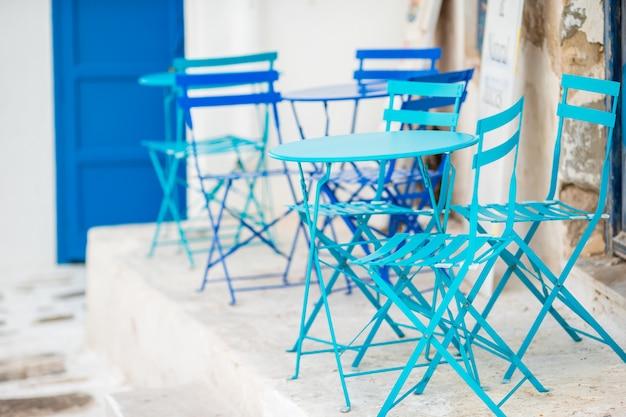 Café im freien auf einer straße des typischen griechischen traditionellen dorfs in griechenland. kaffee am tisch zum frühstück