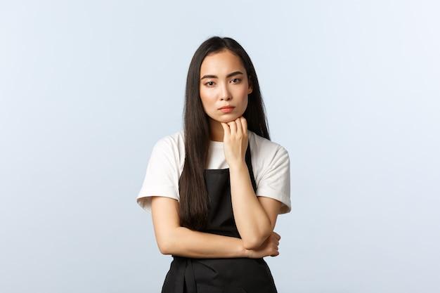 Café, kleinunternehmen und startup-konzept. ernsthaft aussehender nachdenklicher asiatischer cafébesitzer, der denkt, die faust unter das kinn halten und die kamera anstarren, während sie zuhören, stehender weißer hintergrund