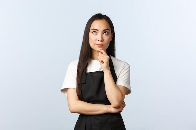 Café, kleinunternehmen und startup-konzept. nachdenklicher junger cafébesitzer, weibliches personal in schwarzer schürze, das nachdenkt, nachdenklich aufschaut, eine entscheidung über den studiohintergrund trifft