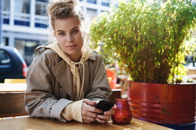 Café-klientin der jungen frau, die draußen sitzt und ein mobiltelefon benutzt.