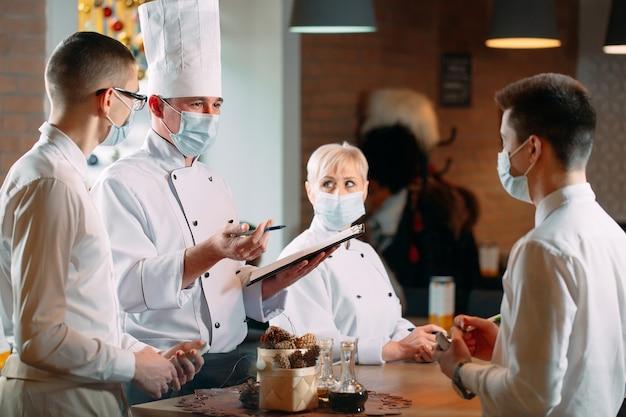 Cafe-mitarbeiter am morgen briefing mit schutzmasken.