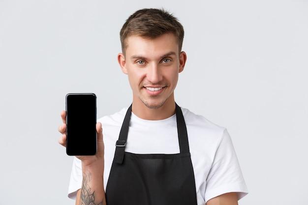 Café und restaurants, cafébesitzer und einzelhandelskonzept. nahaufnahme eines frechen gutaussehenden verkäufers informiert die leute über eine neue app für online-bestellungen, zeigt smartphone-display und lächelt