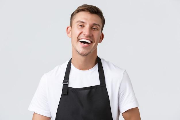 Café und restaurants, cafébesitzer und einzelhandelskonzept. nahaufnahme eines fröhlichen, gutaussehenden verkäufers in schwarzer schürze, der kunden im laden einlädt oder begrüßt, glücklich lachend, weißer hintergrund