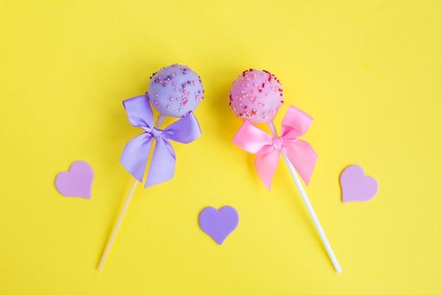 Cake pops mit rosa und violetten schleifen auf dem gelb