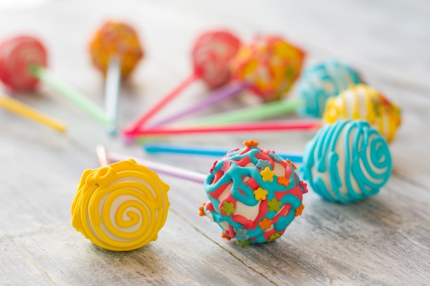 Cake pops mit zuckerguss. verzierte süßigkeiten von heller farbe. bonbons mit weißer schokolade. dessert für ein kind.