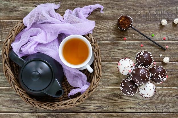 Cake pops. runde süßigkeiten am stiel in schokoladenglasur. eine tasse tee.