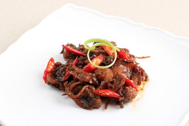 Calamari oder tintenfisch in austernsauce (tumis cumi bumbu kecap), hergestellt aus tintenfisch, gekocht mit chilis, zwiebeln, aroma, tomaten-chilisauce und austernsauce. isoliert auf weißem teller serviert