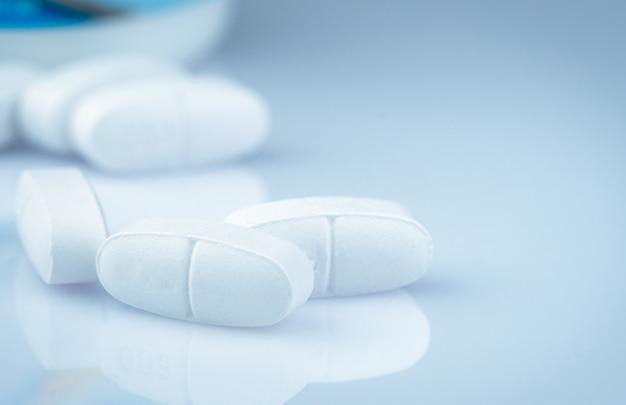 Calciumtabletten für kinder oder schwangere. weiße tablettenpillen auf unscharfem drogenflaschenhintergrund. vitamine und ergänzungskonzept. pharmaindustrie. pharmazeutische produkte. globale gesundheitsversorgung.