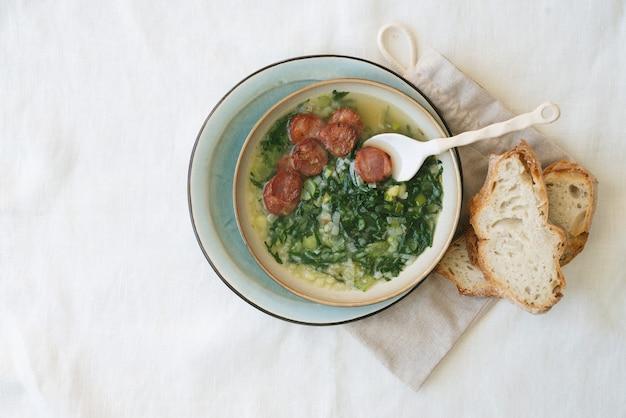 Caldo verde suppe mit gemüse und gehackter chorizo auf der oberseite in keramikschale mit brotstücken. draufsicht