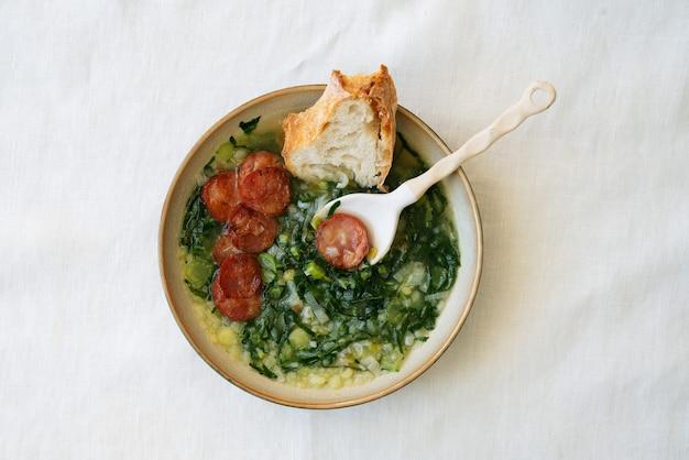 Caldo verde suppe mit gemüse und gehackter chorizo auf der oberseite in keramikschale mit keramiklöffel und stück brot. draufsicht