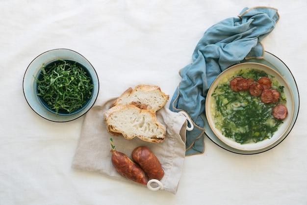 Caldo verde suppe mit gemüse und gehackter chorizo auf der oberseite in keramikschale über einer serviette. draufsicht