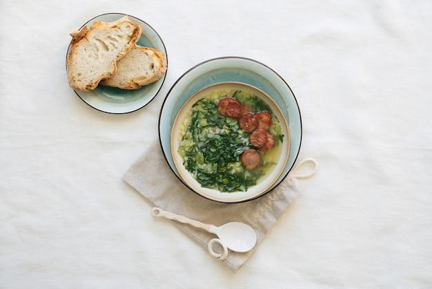 Caldo verde suppe mit gemüse und gehackter chorizo auf der oberseite in keramikschale über keramikplatte auf baumwolltasche mit keramiklöffel. brotstücke auf dem teller. draufsicht