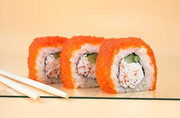 California roll sushi mit gurke, avocado, krabben und orangen-masago auf hellorangefarbenem hintergrund