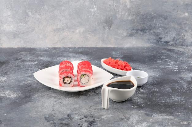 California rolls mit fliegendem fischkaviar auf weißem teller mit ingwer und wasabi