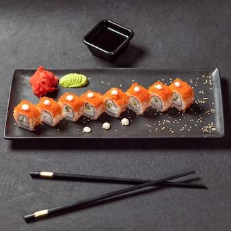 California unagi sushi roll mit soja, wasabi, ingwer und schwarzem essstäbchen