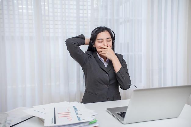 Call-center-betreiber der jungen frau, der bei der arbeit schläfrig sich fühlt.