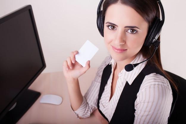 Call-center-frau mit dem kopfhörer, der visitenkarte zeigt.