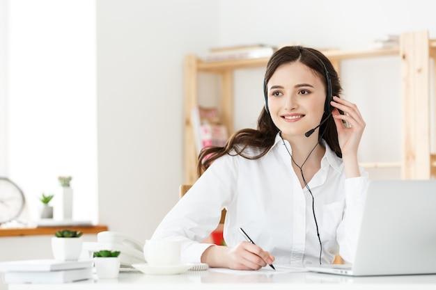 Call center-konzept: porträt eines glücklich lächelnden weiblichen kundenbetreuungs-telefonisten am arbeitsplatz.