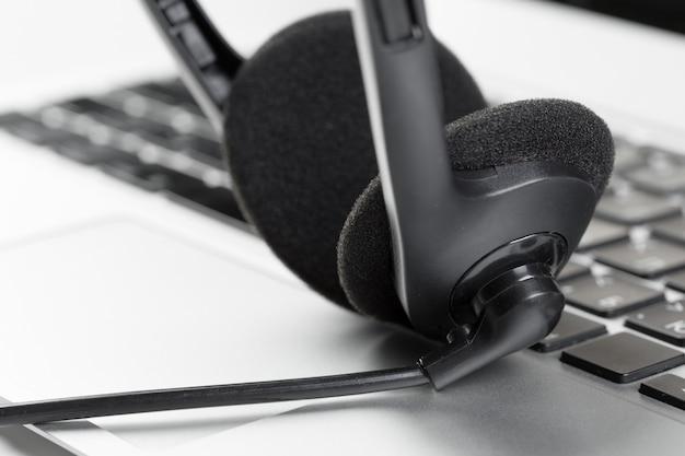 Call-center-stützkonzeptkopfhörer auf tastaturcomputerlaptop