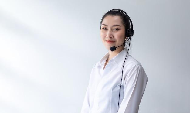 Callcenter-frau auf weißem hintergrund. porträt glückliche asiatische frau operator arbeiten headsets