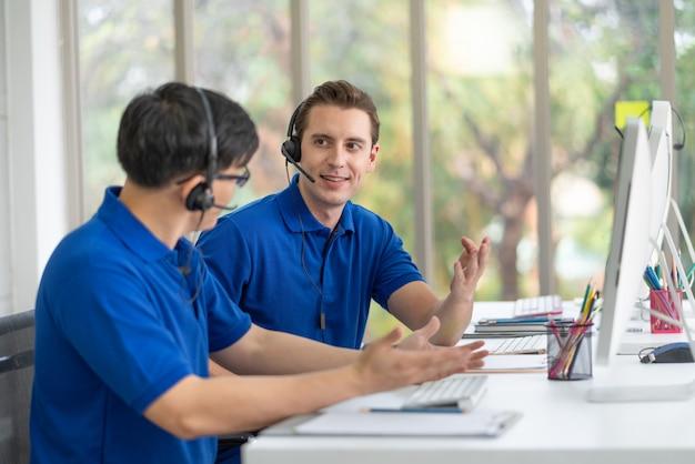Callcenter-mann in blauer hemduniform, der mit kollegen diskutiert