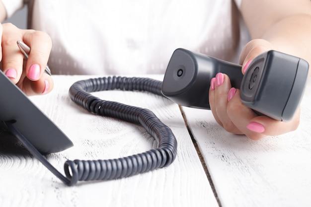 Callcenter- oder bürotelefonkonzept, weibliche fingerpressnummer auf dem telefonblock