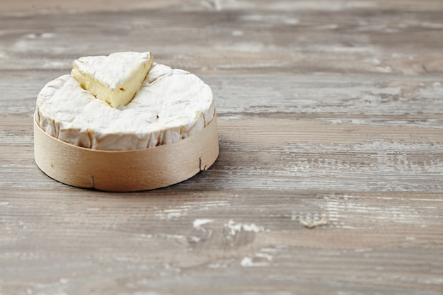 Camembert in holzkiste auf grunge-tisch