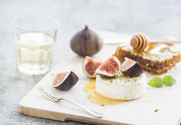 Camembert- oder briekäse mit frischen feigen, bienenwabe und glas weißwein auf umhüllungsbrett über rustikalem grauem hintergrund des schmutzes