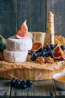 Camembert und blauschimmelkäse stilton mit feigenhonig und trauben.