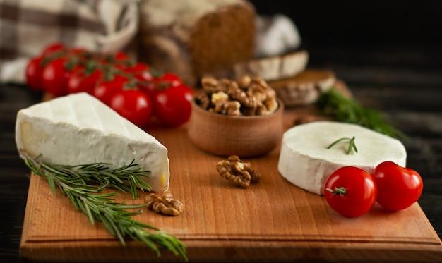 Camembert- und briekäsekäse mit roggenbrot, nüssen, kirschtomaten und rosmarin auf einem hölzernen brett