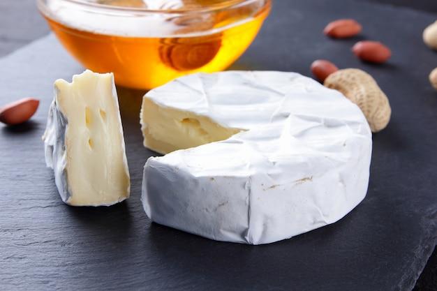 Camembert und honig auf schwarzem schieferbrett. weichkäse mit schimmel und erdnüssen. käse und nüsse auf steinbrett